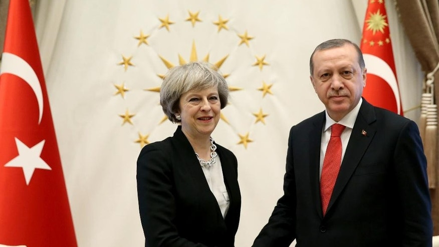 Turkey's President Recep Tayyip Erdogan, right, shakes hands with British Prime Minister Theresa May, prior to their meeting at the Presidential Palace in Ankara, Turkey, Saturday, Jan. 28, 2017. May met with Erdogan and the talks in Ankara will focus on boosting trade between Turkey and Britain once the U.K. leaves the European Union, and on increasing cooperation over security and counterterrorism. May and Turkish leaders are also expected to discuss the conflict in Syria and efforts to reunite Cyprus. (Pool via AP)