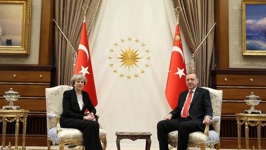 Turkey's President Recep Tayyip Erdogan, right, poses for the photographers with British Prime Minister Theresa May, prior to their meeting at the Presidential Palace in Ankara, Turkey, Saturday, Jan. 28, 2017. May met with Erdogan and the talks in Ankara will focus on boosting trade between Turkey and Britain once the U.K. leaves the European Union, and on increasing cooperation over security and counterterrorism. May and Turkish leaders are also expected to discuss the conflict in Syria and efforts to reunite Cyprus. (Pool via AP)