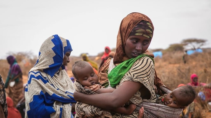 Basherow Hassen, a mother of four, waits for food aid with her twin children in the Warder district in the Somali region of Ethiopia, Saturday, Jan. 28 2017. Ethiopia is struggling to counter a new drought in its east that authorities say has left 5.6 million people in urgent need of assistance. (AP Photo/Mulugeta Ayene)
