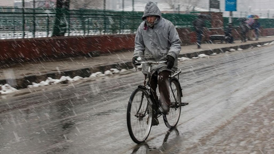 A cyclists rides as it snows in Srinagar, Indian controlled Kashmir, Saturday, Jan. 28, 2017. Authorities in Indian-controlled Kashmir have issued avalanche warnings for many parts of the region, as the heavy snowfall has cut off roads, disrupted power and communication lines, and forced the evacuation of hundreds of residents. (AP Photo/Dar Yasin)