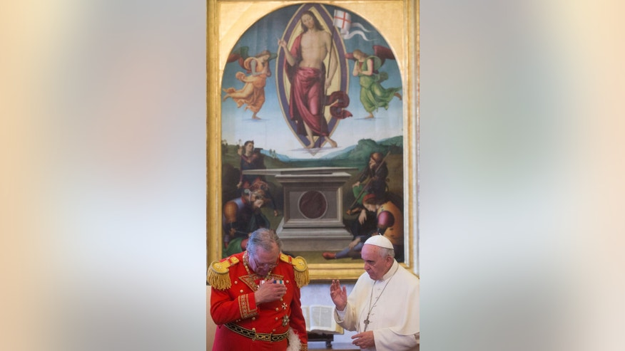 "FILE -- In this  June 20, 2014 file photo, Pope Francis blesses the Grand Master of the Sovereign Order of Malta, Fra' Matthew Festing, during a private audience in the pontiff's private library at the Vatican. The Knights of Malta is still insisting on its sovereignty in its showdown with the Vatican, even after Pope Francis effectively took control of the ancient religious order and announced a papal delegate would govern it through a ""process of renewal."" (AP Photo/Claudio Peri, Pool)"