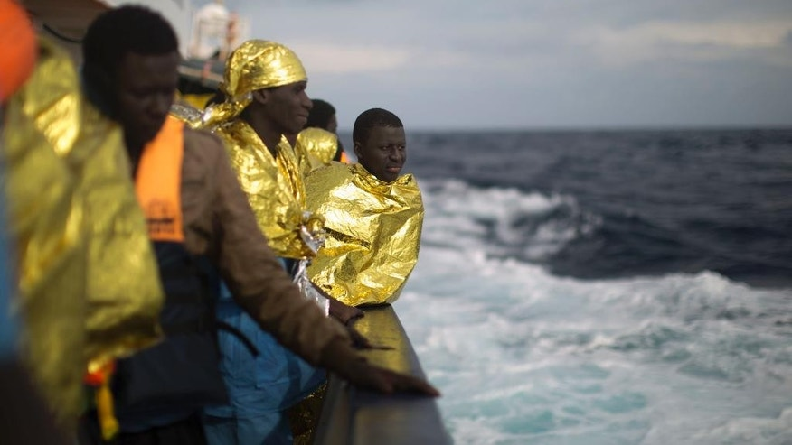 Sub-saharan migrants stand on the deck of the Golfo Azzurro boat after been rescued from a rubber boat by members of Proactive Open Arms NGO, on the Mediterranean sea, about 24 miles north of Sabratha, Libya, Saturday, Jan. 28, 2017. Rescuers pulled nearly 300 people from two rubber boats in waters off the Libyan coast on Friday, and all of them will be transferred to an Italian port in Sicily. (AP Photo/Emilio Morenatti)