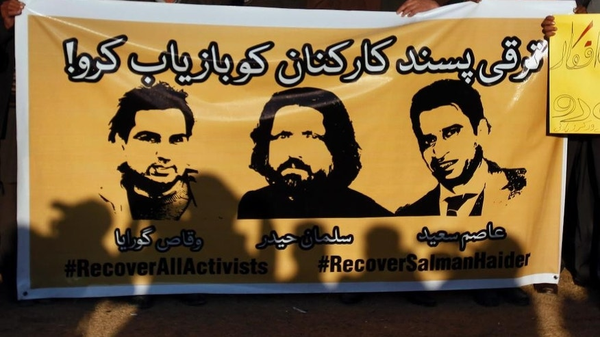 In this Jan. 10, 2017 photo, members of civil society hold a banner with pictures of missing rights activists, Waqas Goraya, Salman Haider, and Asim Saeed, during a demonstration to condemn the missing human rights activists, in Islamabad, Pakistan. Pakistani police and a family member say on Saturday, Jan. 28, 2017 the university professor and rights activist who went missing early this month has returned home safely. (AP Photo/Anjum Naveed)