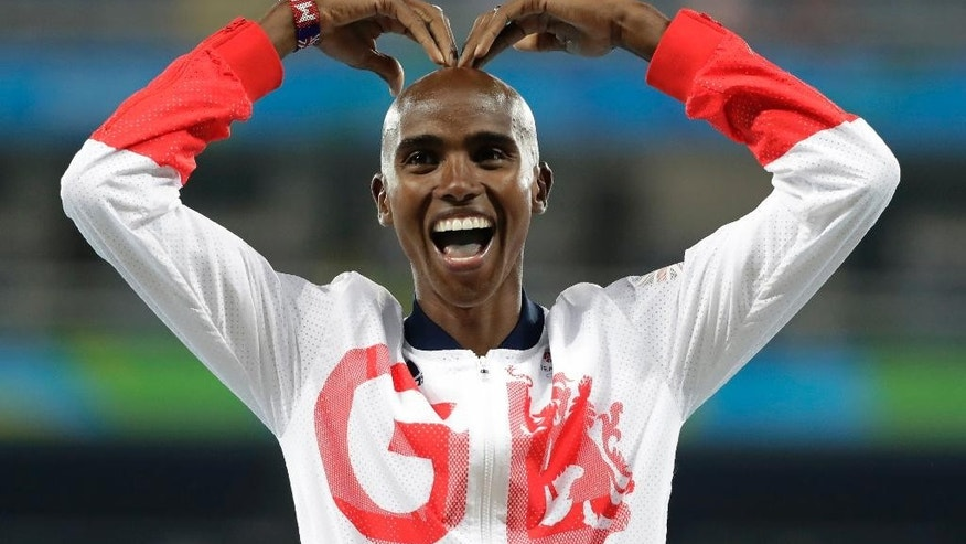 "FILE - A Saturday, Aug. 20, 2016 file photo of Britain's Mo Farah gesturing on the podium as he waits to receive his gold medal for the men's 5000-meter race during athletics events at the Summer Olympics inside Olympic stadium in Rio de Janeiro, Brazil. Four-time Olympic champion Mo Farah has criticized U.S. President Donald Trump's immigration policy, saying Sunday, Jan. 29, 2017, the temporary travel ban ""seems to have made me an alien"" and leaves him unsure whether he can return to his U.S home. Farah is a British citizen who was born in Somalia, one of seven predominantly Muslim nations subject to the executive order signed by Trump that currently bars entry to the United States. (AP Photo/Jae C. Hong, File)"