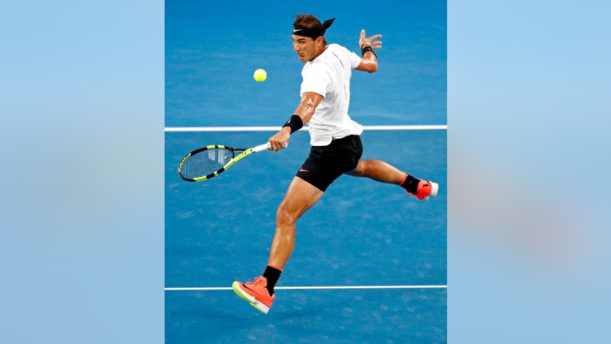 Spain's Rafael Nadal makes a backhand return to Switzerland's Roger Federer during the men's singles final at the Australian Open tennis championships in Melbourne, Australia, Sunday, Jan. 29, 2017. (AP Photo/Dita Alangkara)