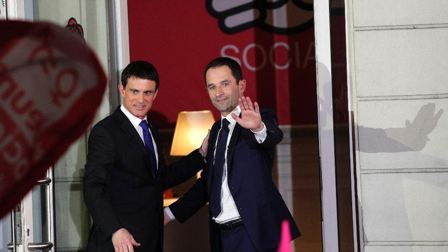 Former Socialist Prime Minister Manuel Valls, left, and Benoit Hamon, wave to supporters at the socialist party headquarters in Paris, Sunday, Jan. 29, 2017. Hamon, riding to victory from left-wing obscurity on a radical proposal to a pay all adults a monthly basic income, will be the Socialist Party candidate in France's presidential election after handily beating Valls in a primary runoff vote. (AP Photo/Christophe Ena)