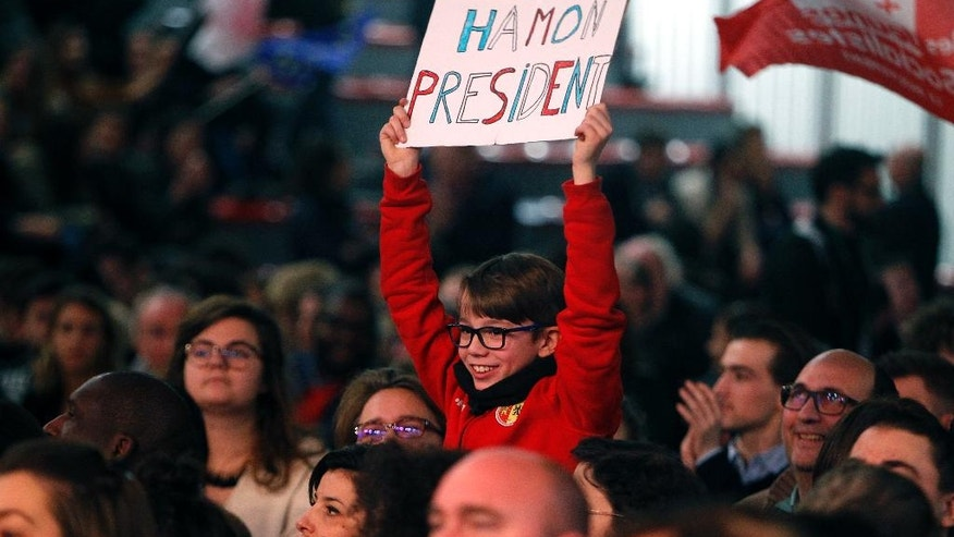 A young boy holds a placard during a meeting of the candidate for the left-wing presidential primaries Benoit Hamon in Lille, Northern France, Friday, Jan. 27, 2017. Manuel Valls, a center-leaning former prime minister who rallied France together after extremist attacks, will confront stalwart Socialist Benoit Hamon in the country's left-wing presidential primary runoff Sunday. (AP Photo/Michel Spingler)