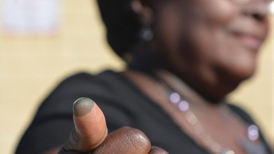 Benite Oramise shows her ink-stained thumb, marked by election workers to indicate she voted, at a polling station in the Bel Air neighborhood of Port-au-Prince, Haiti, Sunday, Jan. 29, 2017. Haiti is holding a final round of legislative contests that close a repeatedly derailed election cycle that started in 2015. (AP Photo/David McFadden)