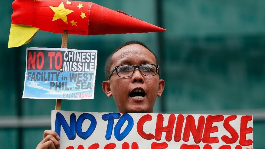 "FILE - In this Jan. 24, 2017 file photo, an environmental activist shouts slogans while displaying placard and a mock missile during a rally at the Chinese Consulate to protest alleged military build-up by China on the disputed group of islands at the South China Sea, in the financial district of Makati, east of Manila, Philippines. In their statement, the protesters condemned the alleged China's installation of missile system across the disputed Spratlys group of islands and urged the Chinese government that ""reefs not rockets should be proliferating in the ecologically-critical waters of the islands."" (AP Photo/Bullit Marquez, File)"