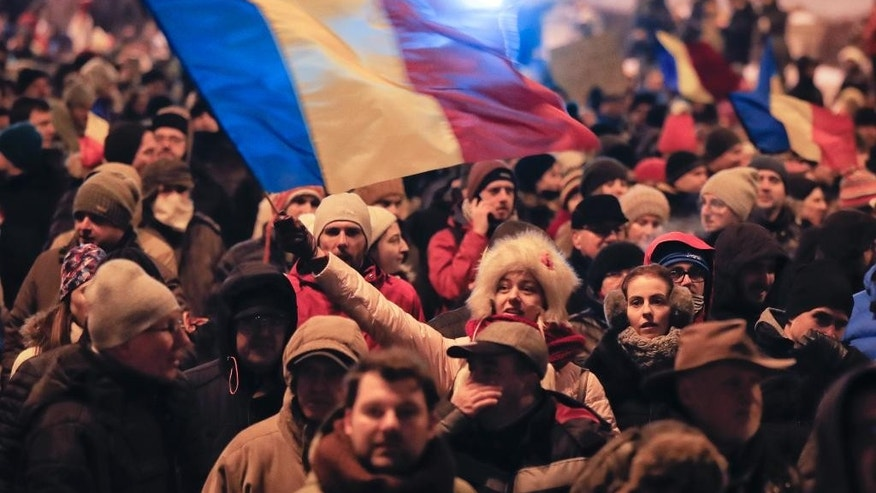 A woman waves a flag as protesters march outside the Justice Ministry in Bucharest, Romania, Sunday, Jan. 29, 2017. Some 10.000 people marched through the Romanian capital and other cities to protest a government proposal to pardon thousands of prisoners which critics say could reverse the anti-corruption fight.(AP Photo/Vadim Ghirda)