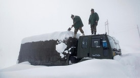Indian Army soldiers clear snow from their stranded vehicle near a base camp in Gulmarg, about 55 kilometres (34 miles) northwest of Srinagar, Indian controlled Kashmir, Friday, Jan. 27, 2017. The death toll from two avalanches that struck the Himalayan region of Kashmir has risen to more than a dozen as the bodies of four more Indian soldiers were recovered, the Indian army said Friday. Authorities in Indian-controlled Kashmir have issued avalanche warnings for many parts of the region, as the heavy snowfall has cut off roads, disrupted power and communication lines, and forced the evacuation of hundreds of residents. (AP Photo/Dar Yasin)