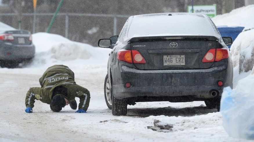 A police officer looks for evidence under a car in the area of a Quebec City mosque on Monday, Jan. 30, 2017. A shooting at a Quebec City mosque Sunday night left multiple dead and injured. One suspect was arrested at the scene and another nearby. (Paul Chiasson/The Canadian Press via AP)