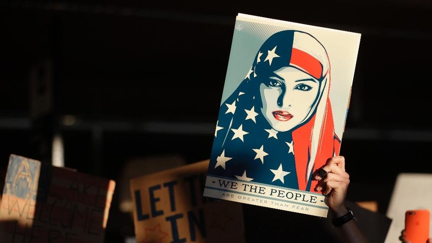 "FILE- In this Saturday, Jan. 28, 2017 file photo, a protester holds a sign at San Francisco International Airport during a demonstration to denounce President Donald Trump's executive order that bars citizens of seven predominantly Muslim-majority countries from entering the U.S., in San Francisco. Just two days after banning travelers from seven Muslim-majority nations, U.S. President Donald Trump invited the Saudi monarch, whose kingdom includes Islam's holiest sites, to fly to Washington. It points to the delicate balancing act Trump faces as he tries to deliver on campaign promises to exterminate ""radical Islamic terrorism"" without endangering political and economic ties with U.S. allies in the region, many of which are countries where the Trump Organization has business interests. (AP Photo/Marcio Jose Sanchez, File)"