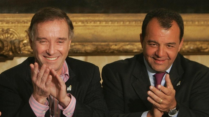 FILE- In this April 7, 2009, file photo, Brazil's businessman Eike Batista, left, and Rio de Janeiro's governor Sergio Cabral attend a ceremony in which Batista donated R$ 10'000,000.00, around US$ 4.5 US million dollars, for the the Rio 2016 Olympic games bid in Rio de Janeiro, Brazil. Federal police on Thursday, Jan. 26 2017, issued an arrest warrant for Batista for allegedly paying bribes to former Rio state Gov. Sergio Cabral to gain advantage in government contracts. Cabral is facing several corruption charges and was jailed in 2016. (AP Photo/Ricardo Moraes, File)