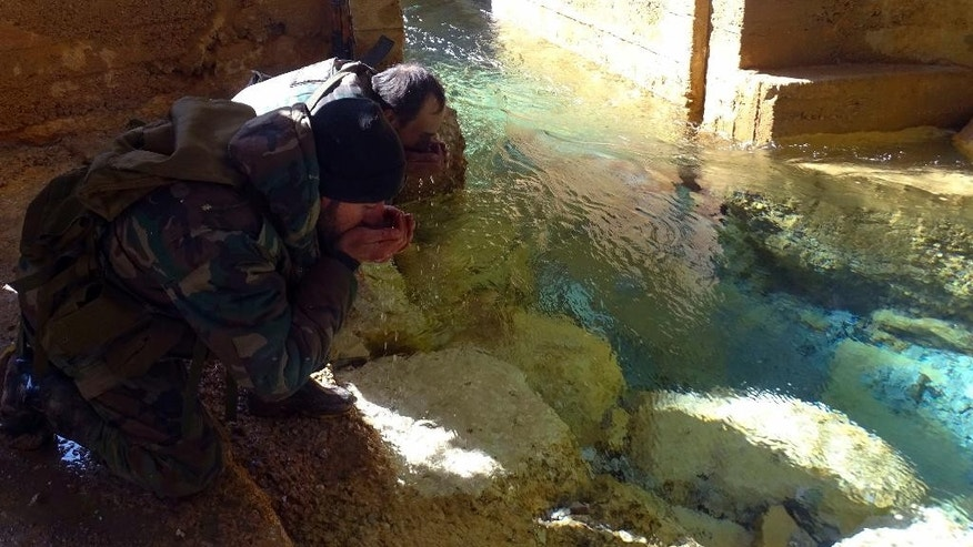 In this photo released on Sunday Jan. 29, 2017, by the Syrian official news agency SANA, Syrian soldiers drink from the Ein al-Fijeh spring which supplies the capital by water, northwest of Damascus, Syria. Syrian state TV reported later Monday that pumping water to some neighborhoods of the capital resumed after technical teams fixed some of the pumps at the Ein al-Fijeh spring. It said work is ongoing to fix all pumping stations in the area in what would mark an end to the weeks-long water crisis. (SANA via AP)