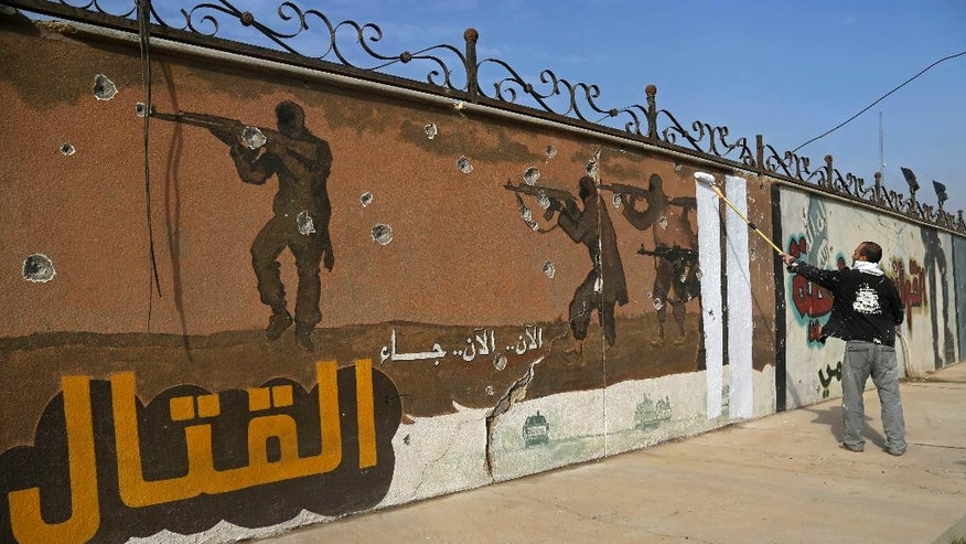 "A volunteer paints over a mural that had been displayed by the Islamic State group, on the eastern side of Mosul, Iraq, Monday, Jan. 30, 2017. Arabic reads, ""Now the fighting begins."" (AP Photo/Khalid Mohammed)"
