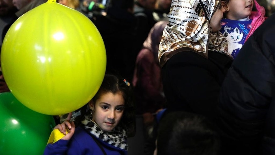 Sima, a 7-year-old Syrian refugee from Homs, plays with a balloon as her mother M'aha Aleweir holds her 3-year old sister Sidra upon their arrival at Rome's Fiumicino international airport, Monday, Jan. 30, 2017. Italian government and church officials have welcomed 41 Syrian refugees at Rome's airport, saying they wanted to show solidarity at a time when the United States is sending refugees away and building walls to keep them out. (AP Photo/Alessandra Tarantino)