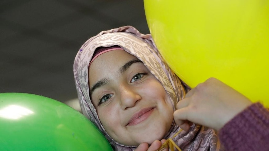 Haya, a 13 year-old Syrian refugee from Homs, plays with balloons upon her arrival at Rome's Fiumicino international airport, Monday, Jan. 30, 2017. Italian government and church officials have welcomed 41 Syrian refugees at Rome's airport, saying they wanted to show solidarity at a time when the United States is sending refugees away and building walls to keep them out. (AP Photo/Alessandra Tarantino)