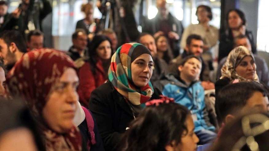Syrian refugees sit during an official welcome ceremony at Rome's Fiumicino international airport, Monday, Jan. 30, 2017. Italian government and church officials have welcomed 41 Syrian refugees at Rome's airport, saying they wanted to show solidarity at a time when the United States is sending refugees away and building walls to keep them out. (AP Photo/Alessandra Tarantino)