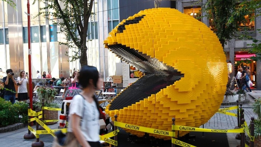 "FILE - In this Aug. 12, 2015, file photo, a woman walks past a three-meter (nine-foot)-tall Pac-Man made of Lego bricks, in Tokyo's Shinjuku area. Masaya Nakamura, the ""Father of Pac-Man"" who founded the Japanese video game company behind the hit creature-gobbling game, has died on Jan. 22, 2017, at age 91, the company Bandai Namco said. (AP Photo/Ken Aragaki, File)"