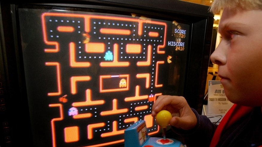 "FILE - In this Oct. 5, 2004, file photo, Jake Gautney, 12, of Chappaqua, N.Y., tries a Ms. Pac-Man game at the Toy Industry Association holiday preview in New York. Masaya Nakamura, the ""Father of Pac-Man"" who founded the Japanese video game company behind the hit creature-gobbling game, died on Jan. 22, 2017. He was 91. (AP Photo/Richard Drew, File)"