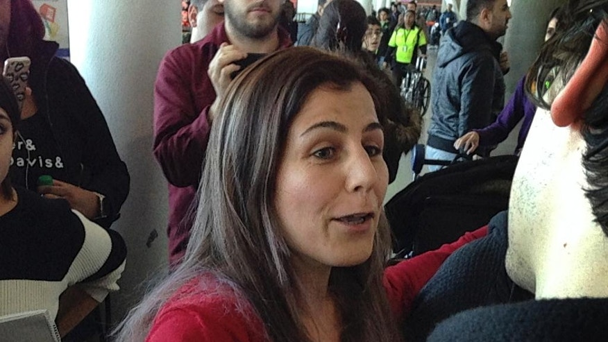 Vahideh Rasekhi, an Iranian doctoral student at Stony Brook University, greets friends and family as she is released from detention at John F. Kennedy International Airport in New York, Sunday, Jan. 29, 2017. (AP Photo/Seth Wenig)