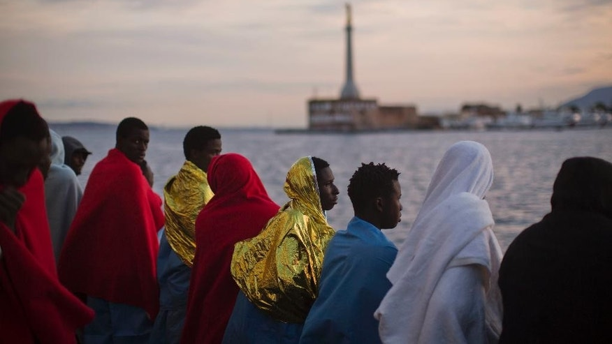 Wrapped in blankets, Sub-Saharan migrants look at the coast inside the Golfo Azzurro rescue vessel as they are arriving at the port of Messina, in Italy, with more than 299 migrants aboard the ship rescued by members of Proactive Open Arms NGO, on Sunday, Jan. 29, 2017. (AP Photo/Emilio Morenatti)