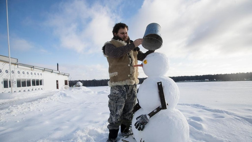 "In this photo taken on Wednesday, Jan. 25, 2017, Russian cheesemaker Oleg Sirota puts a bucket on top a snowman in Istra district, about 80 kilometers outside Moscow, Russia. Sirota is one of Russia's winners from international sanctions. Russian businessman Oleg Sirota is such a big fan of Donald Trump that he's built a ""Trump"" snowman outside his factory _ but he fears the new U.S. president will ruin his life's work. (AP Photo/Pavel Golovkin)"