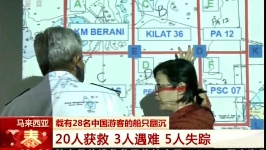 In this image made from video run by China's CCTV via AP Video, Chinese and Malaysian officials look at a search grid of the area a boat sunk, in Kota Kinabalu, Sabah, Malaysia. in Kota Kinabalu, Sabah, Malaysia, Monday, Jan. 30, 2017. Malaysian authorities expanded the search Monday still missing two days after their boat sank off Borneo island. (CCTV via AP)