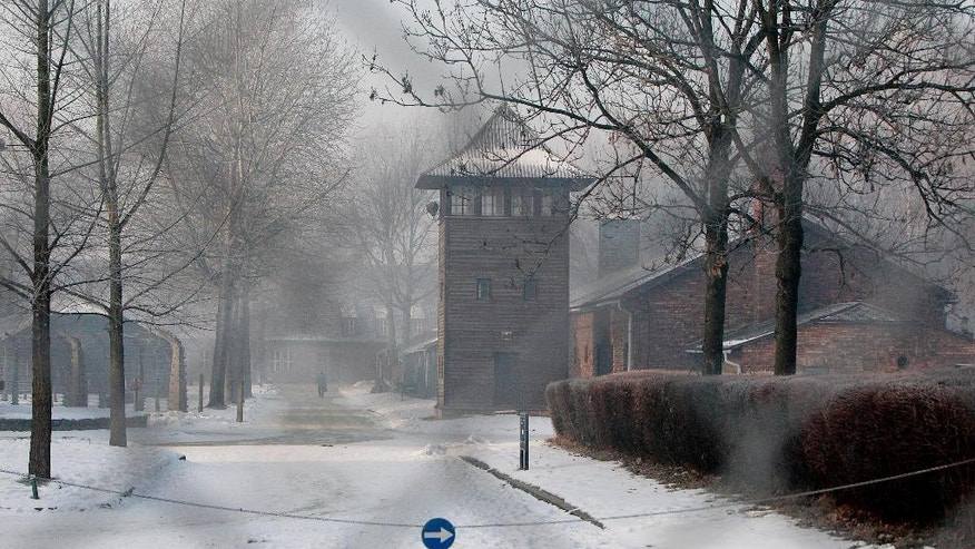 This photo taken taken through a metal fence on Friday, Jan. 27, 2017 in Oswiecim, Poland, shows a guard's tower of the former Nazi German death camp of Auschwitz that the Nazis operated in occupied Poland during World War II. Poland's historians have put online what they say is the most complete list of Nazi SS commanders and guards at Auschwitz, in hopes some of them can still be brought to justice. (AP Photo/Czarek Sokolowski)