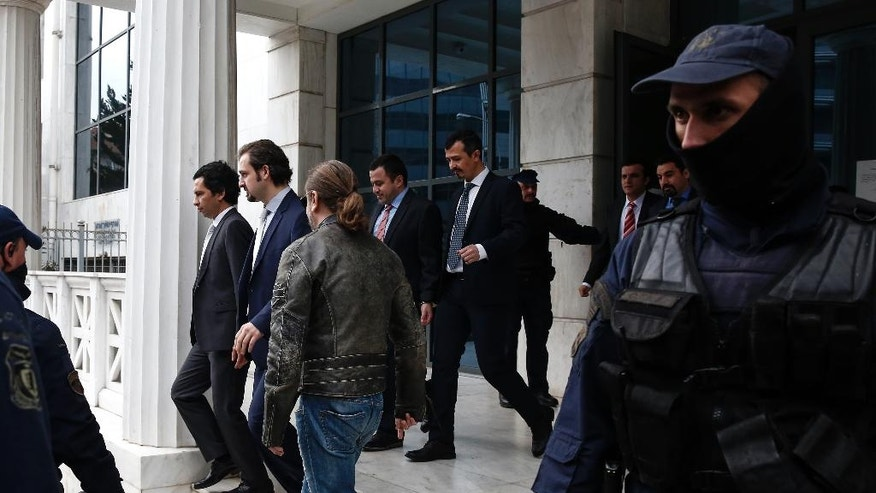 Four of eight Turkish military officers, center, leave an Administrative Court in Athens, Monday, Jan. 30, 2017. The Turkish servicemen appeared at the court to express their objection about the decision of the Greek state to remain in custody for three more months following the rejection of the extradition request by the Supreme Court. (AP Photo/Yorgos Karahalis)