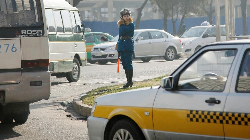 FILE - In this Dec. 1, 2015, file photo, a North Korean traffic police officer directs vehicles in Pyongyang, North Korea. The streets of Pyongyang are more crowded than ever, but Pyonghwa Motors, North Korea's only passenger car company, whose sole factory was designed to produce as many as 10,000 cars a year, appears to be stuck in neutral. (AP Photo/Wong Maye-E, File)