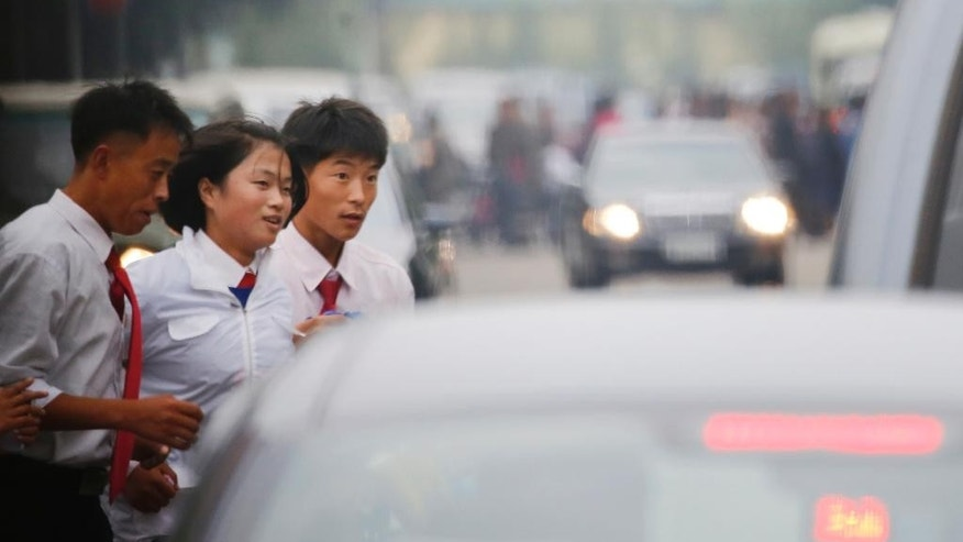 In this Oct. 8, 2015, photo, students watch the traffic as they cross a street in Pyongyang, North Korea. The streets of Pyongyang are more crowded than ever, but Pyonghwa Motors, North Korea's only passenger car company, whose sole factory was designed to produce as many as 10,000 cars a year, appears to be stuck in neutral. (AP Photo/Charles Dharapak)