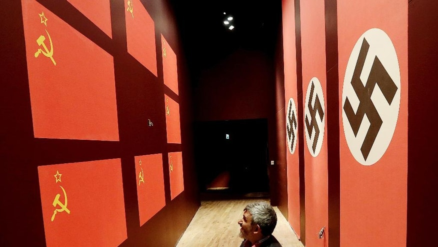 In this photo taken Jan. 23, 2017, a man visits the new Museum of the Second World War in Gdansk, Poland. The museum is at the center of a battle over history between its creators, who tell the history of the war by focusing on the suffering of different nations affected, and Poland's nationalist government, which seeks to take control of the museum to change its content to focus it on Polish suffering and military heroism. A court's decision this week has allowed the museum to exist independently for at least a few more weeks. (AP Photo/Czarek Sokolowski)