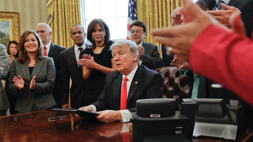 "Small business leaders applaud President Donald Trump after he signed an executive order in the Oval Office of the White House in Washington, Monday, Jan. 30, 2017. Trump order is aimed at significantly cutting regulations. White House officials are calling the directive a ""one in, two out"" plan. It requires government agencies requesting a new regulations to identify two regulations they will cut from their own departments. (AP Photo/Pablo Martinez Monsivais)"