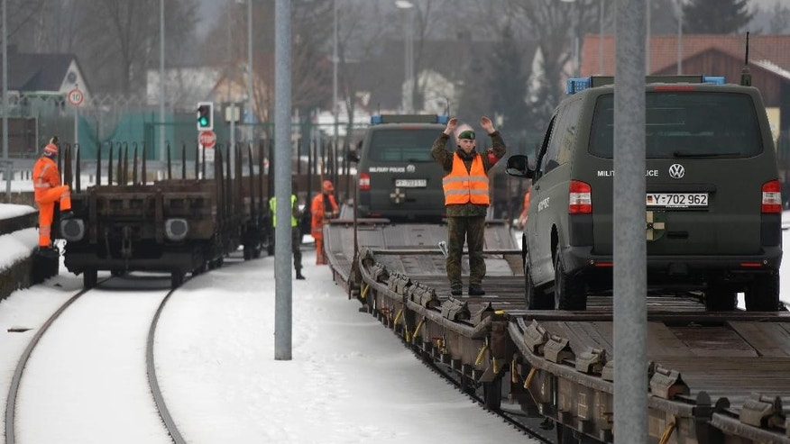 Military vehicles are being loaded on a transport train in Grafenwoehr, Germany, Tuesday, Jan. 31, 2017. As part of the NATO program 'enhanced forward presence' 450 soldiers will move to Rukla in Lithuania in the upcoming weeks. (AP Photo/Matthias Schrader)