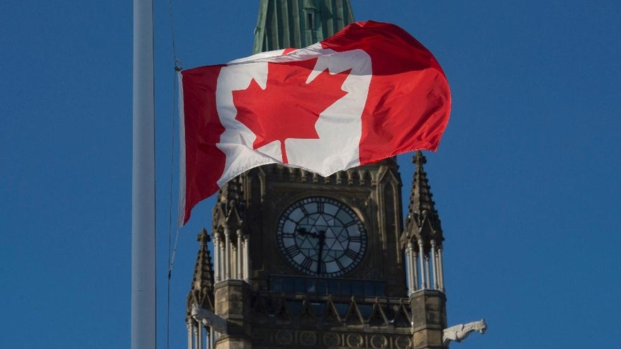 The flag flies at half-mast on the Peace tower Monday Jan. 30, 2017 in Ottawa. It was announced Monday that the flag would fly at half-mast in memory of the victims of the Quebec City shooting.(Adrian Wyld/The Canadian Press via AP)