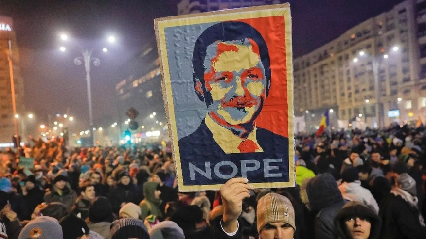 A man holds a poster depicting the leader of the ruling Social Democratic party Liviu Dragnea, during a protest in Bucharest, Romania, early Wednesday, Feb. 1, 2017. Romania's government adopted an emergency ordinance late Tuesday to decriminalize official misconduct, dealing a blow to a yearlong drive to curb corruption in the eastern European country. Justice Minister Florin Iordache said the measure will decriminalize cases of official misconduct in which the financial damage is valued at less than 200,000 lei ($47,800). Tens of thousands of Romanians protested against the ordinance in recent weeks, saying it would weaken anti-graft efforts. (AP Photo/Vadim Ghirda)