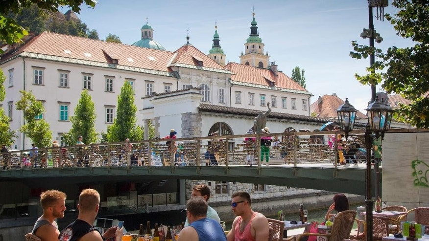 FILE - In this file photo dated Aug. 12, 2016, a group of tourists drink beer on the banks of a waterway in central Ljubljana, Slovenia, transformed into a lively and picturesque city filled with restaurants, cafes and night clubs packed with foreigners. The tiny European nation of Slovenia is undergoing a tourism boom partly because it is the native country of U.S. first lady Melania Trump. (AP Photo/Darko Bandic, FILE)