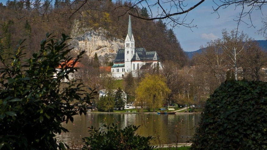 In this Tuesday, April 16, 2013 file photo, a church is pictured on the shore of lake Bled, northern Slovenia. The tiny European nation of Slovenia is undergoing a tourism boom partly because it is the native country of U.S. first lady Melania Trump. (AP Photo/Darko Bandic, File)