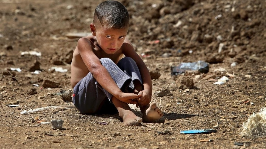 FILE - In this Sept. 11, 2013 file photo, a Syrian refugee boy sits on the ground at a temporary refugee camp, in the eastern Lebanese town of Al-Faour, Bekaa valley near the Syria-Lebanon border. On Tuesday, Jan. 31, 2017, UNICEF appealed for $3.3 billion this year to help millions of children worldwide facing conflict, malnutrition and other humanitarian emergencies. (AP Photo/Hussein Malla, File)