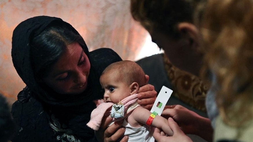 FILE - In this March 11, 2014 file photo, an aid worker measures the upper arm circumference of 9-month-old Shurouk as her mother Mervat, 31, holds her inside their tent at a camp for Syrian refugees in Kab Elias, in Lebanon's Bekaa Valley. The measurement is an immediate indicator of malnourishment. On Tuesday, Jan. 31, 2017, UNICEF appealed for $3.3 billion this year to help millions of children worldwide facing conflict, malnutrition and other humanitarian emergencies. (AP Photo/Bilal Hussein, File)