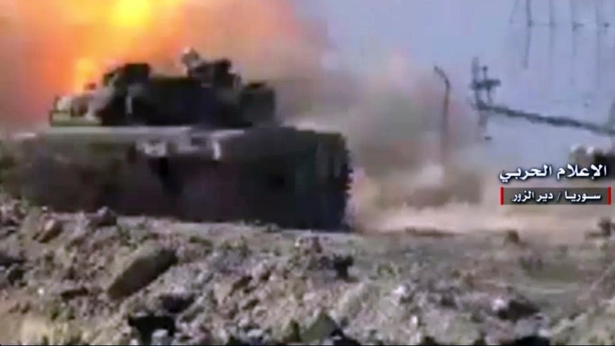 "In this Sunday, Jan. 30, 2017 frame grab from video provided by the government-controlled Syrian Central Military Media, a Syrian forces tank fires on an Islamic State group's position, in Deir al-Zour, north Syria. The World Food Program said Tuesday that it has resumed food airdrops to Deir al-Zour, in eastern Syria, after the Islamic State group renewed its assault on the city two weeks ago. Rebels, al-Qaida linked insurgents, IS militants, and government forces and loyal militias are all skirmishing for control of Syria's southern provinces. Arabic reads, ""Central Military Media, Deir al-Zour, Syria."" (Syrian Central Military Media, via AP)"