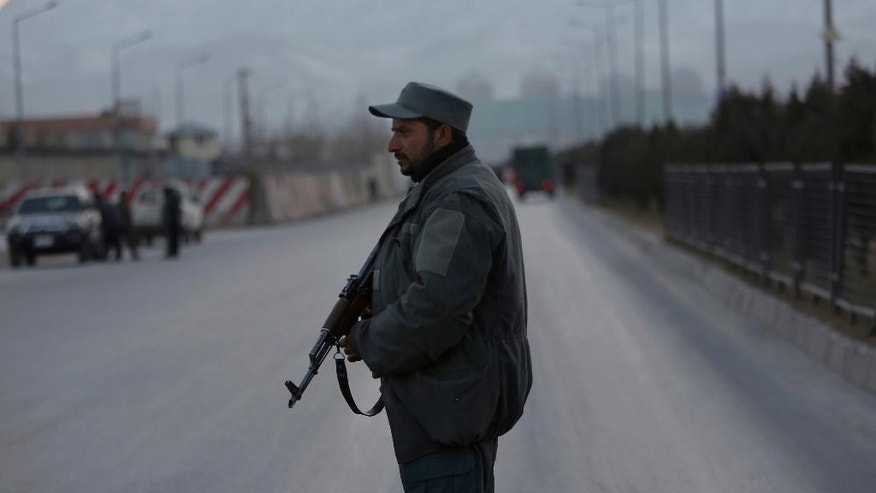 FILE - In this Tuesday, Jan. 10, 2017, file photo a member of the Afghan security forces stands guard near the site of two blasts in Kabul, Afghanistan. In its first report to the Trump administration, a U.S. watchdog issues a bleak report saying the Afghan government controls barely half the country, its security forces numbers are declining and drug production is on the rise, while eradication is down. (AP Photo/Rahmat Gul, File)