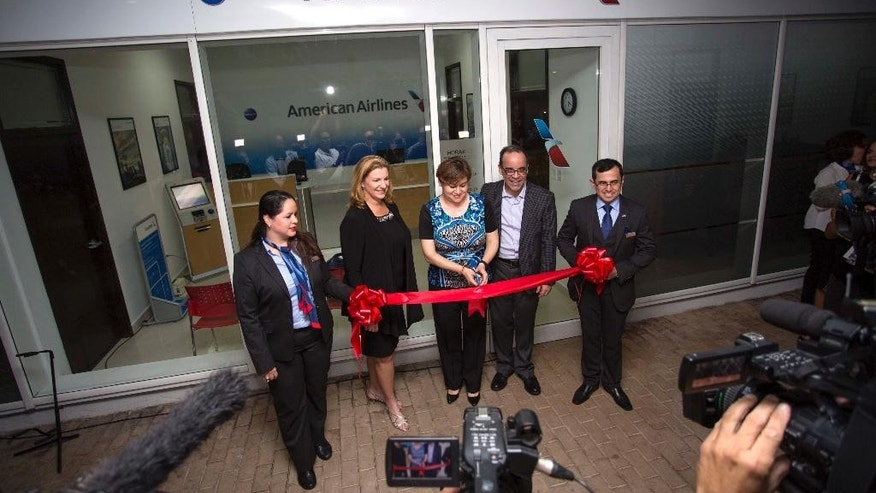 American Airlines Regional Sales Director Christine Valls, second from left, Regional Operations Manager Lorena Sandoval, center, and Cuba Operations chief Galo Beltran, second from right, along with local staff, take part in a ribbon cutting ceremony outside American Airlines' new office in Havana, Cuba, Wednesday, Feb. 1, 2017.  American Airlines has opened an office in Havana and officials say they will move ahead with their plans for Cuba despite uncertainty over what President Donald Trump's administration will bring. (AP Photo/Desmond Boylan)