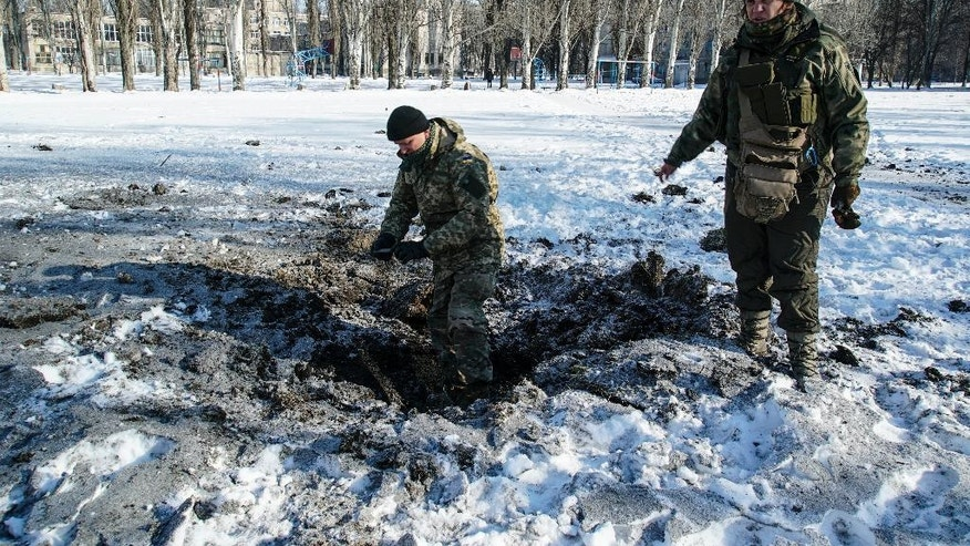 A Ukrainian soldier inspects a crater left by an explosion in Avdiivka, Ukraine, Tuesday, Jan. 31, 2017. Fighting between government troops and Russia-backed separatist rebels in eastern Ukraine escalated on Tuesday, killing at least eight people late Monday and early Tuesday, injuring dozens and briefly trapping more than 200 coal miners underground, the warring sides reported.(AP Photo/Inna Varenytsia)
