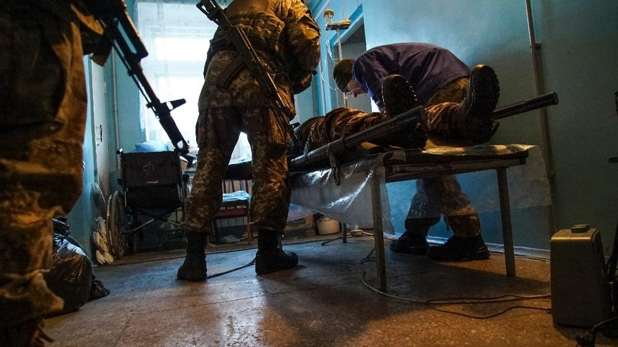 A wounded Ukrainian soldier is treated in a hospital in Avdiivka, Ukraine, Tuesday, Jan. 31, 2017. Fighting between government troops and Russia-backed separatist rebels in eastern Ukraine escalated on Tuesday, killing at least eight people late Monday and early Tuesday, injuring dozens and briefly trapping more than 200 coal miners underground, the warring sides reported.(AP Photo/Inna Varenytsia)