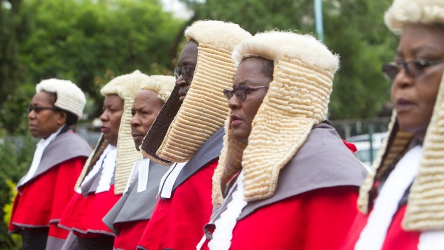 Zimbabwean judges in long red robes and horsehair wigs, a throwback to an era of British Colonial rule, at the official beginning of their 2017 duties, in Harare, Monday Jan. 16, 2017. President Robert Mugabe has sparred with Britain for decades and denounces the West for what he calls a neo-colonial attitude, but he has a soft spot for a traditional etiquette and a dress code in the courts that even Britain has partly dropped. (AP Photo/Tsvangirayi Mukwazhi)