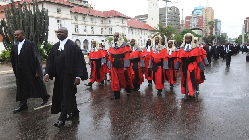 Zimbabwean judges in long red robes and horsehair wigs, a throwback to an era of British Colonial rule, walk to court for the official beginning of their 2017 duties, in Harare, Monday Jan. 16, 2017. President Robert Mugabe has sparred with Britain for decades and denounces the West for what he calls a neo-colonial attitude, but he has a soft spot for a traditional etiquette and a dress code in the courts that even Britain has partly dropped. (AP Photo/Tsvangirayi Mukwazhi)