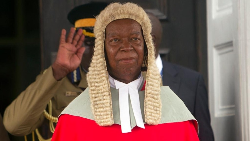 Zimbabwean Chief Justice Godfrey Chidyausiku in a long red robe and horsehair wig, a throwback to an era of British Colonial rule, stands outside the courthouse at the official beginning of 2017 duties, in Harare, Monday Jan. 16, 2017. President Robert Mugabe has sparred with Britain for decades and denounces the West for what he calls a neo-colonial attitude, but he has a soft spot for a traditional etiquette and a dress code in the courts that even Britain has partly dropped. (AP Photo/Tsvangirayi Mukwazhi)